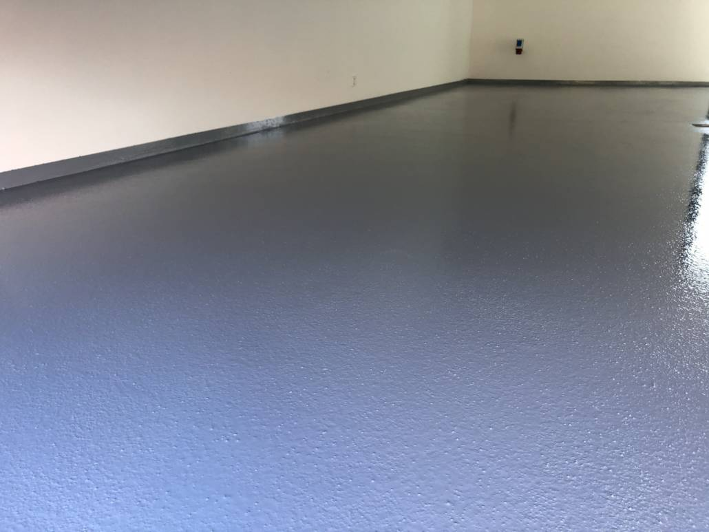 Gråt epoxygulv i privat garage med 6cm frise